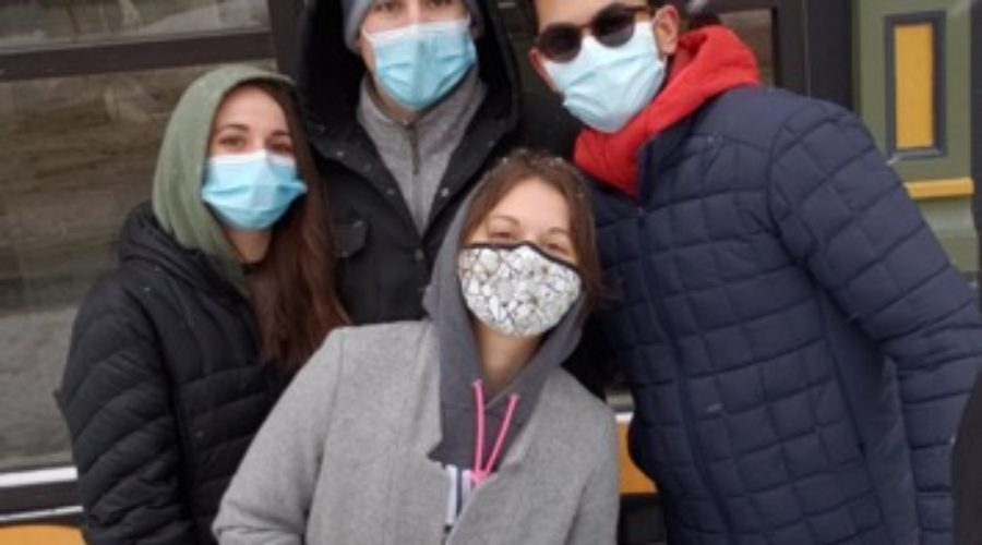 Four students standing together wearing masks, bundled up in winter clothes and scarves